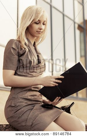 Young fashion business woman with a folder against office windows