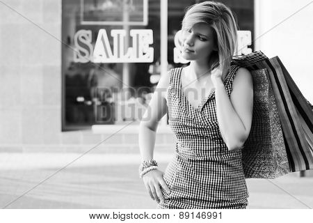 Happy young fashion woman with shopping bags against a mall windows