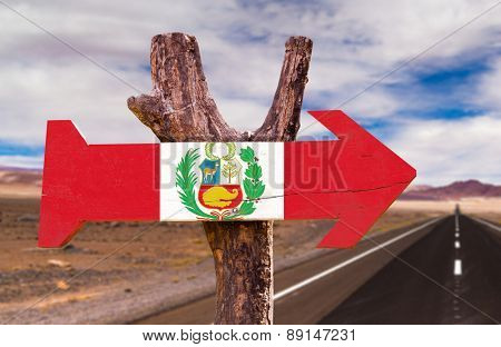 Peru Flag wooden sign with a desert road on background