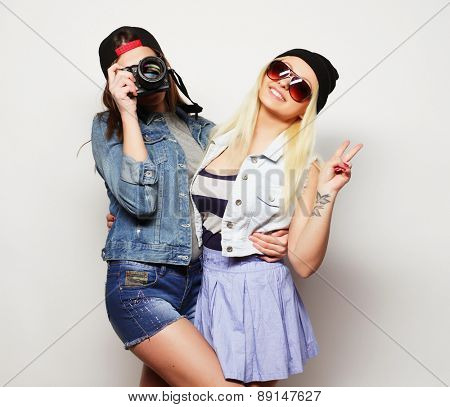 Two girls with cameras in hipster style over grey background