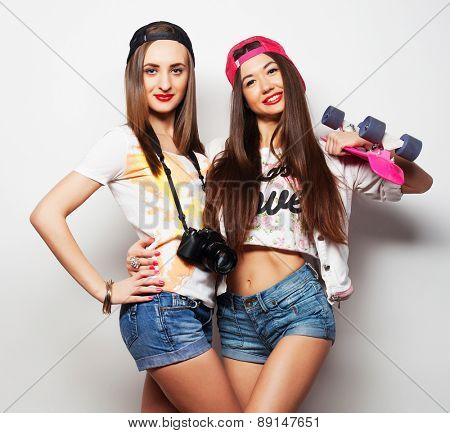Two girl skaters go crazy and have fun together. Beautiful sporty women, positive emotion. Grey background.