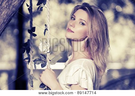 Young fashion blond woman in a city park