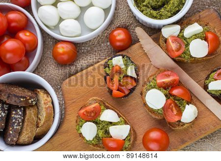 Bruschetta with fresh tomatoes, mozzarella and  herb pesto