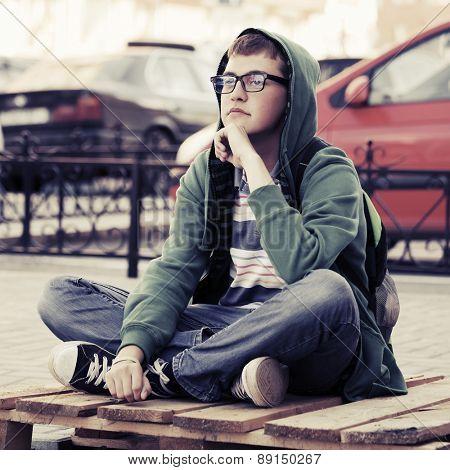 Portrait of young fashion man sitting on a city sidewalk
