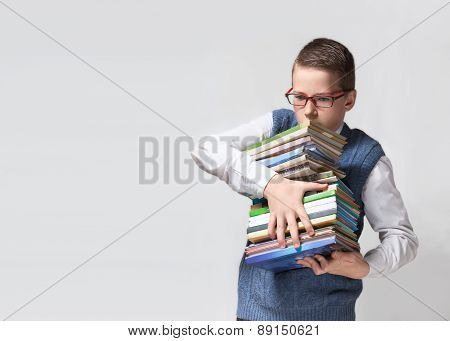 Schoolboy in glasses with stack of books