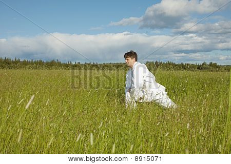 Man Does Exercises In Field