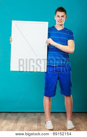 Man Holding Blank Presentation Board On Blue