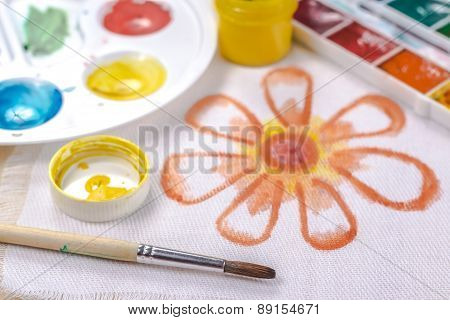 artists brush on a background painted orange flower