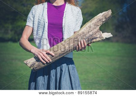 Woman Standing On Grass With A Log