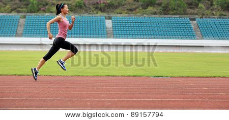 young fitness woman runner running on track