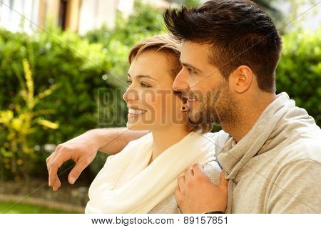 Happy young couple embracing outdoors, smiling. Side view.