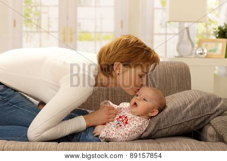 Young mother kissing baby girl, playing on sofa.