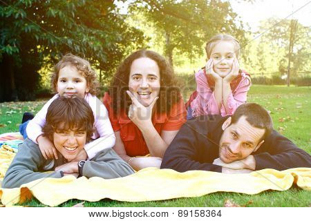 Beautiful happy family enjoying the outdoor park.