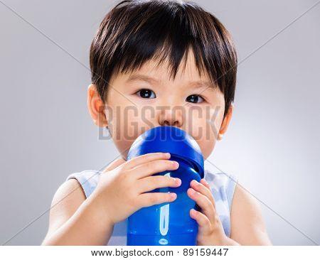Baby boy drinking water using plastic bottle