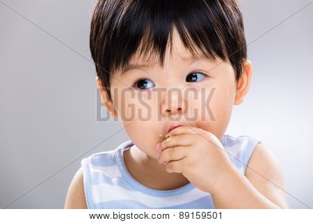 Close up of baby boy eating the finger food