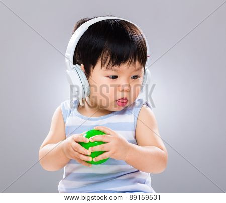 Young boy listen to the song and play with the green ball