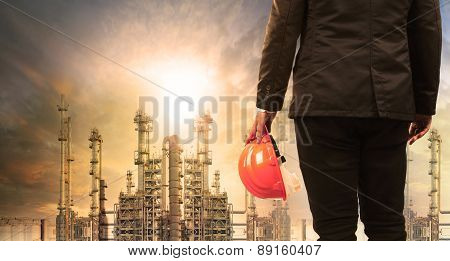 Engineering Man With Safety Helmet Standing In Industry Estate Against Sun Rising Above Oil Refinery