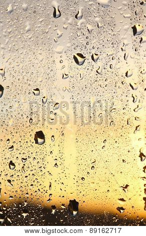 Rain drops on glass. The sunset in background