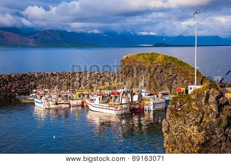 Sunset on the sea fjord in Iceland. White fishing boat in the harbor pier village Arnastapi