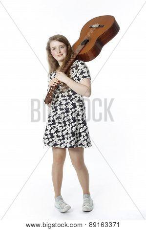 Smiling Teenage Girl In Dress Holds Guitar On Shoulder In Studio
