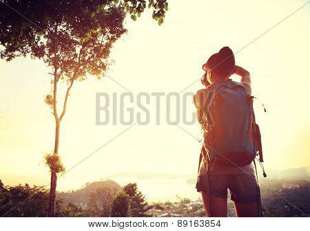 woman hiker taking photo at mountain peak