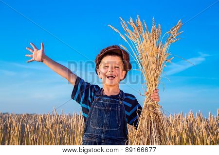 Happy farmer's boy on wheat field