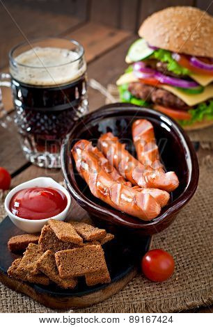 Grilled sausages, crackers and beer on a wooden background in rustic style