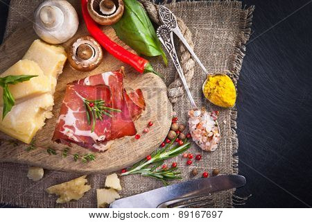 Various cheeses, salami and mushrooms on the wooden board