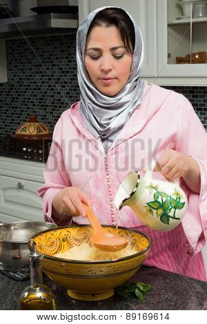 Moroccan immigrant woman in modern European kitchen preparing couscous for Ramadan nights