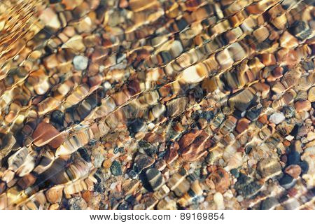 Stones On The Seabed Through The Small Waves