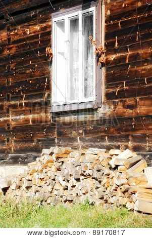 firewood stacked by the window, near a wooden house