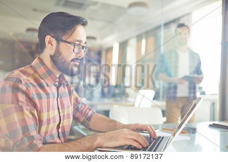 Male office worker browsing in laptop