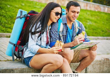 Young man and woman with rucksacks and map choosing travel route