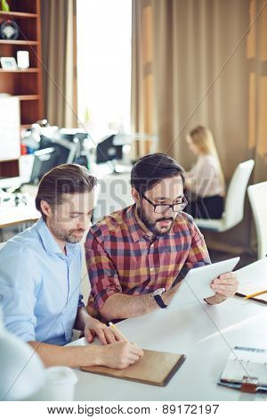 Two male employees planning work at meeting