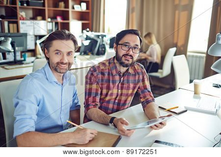 Two male colleagues looking at camera at workplace