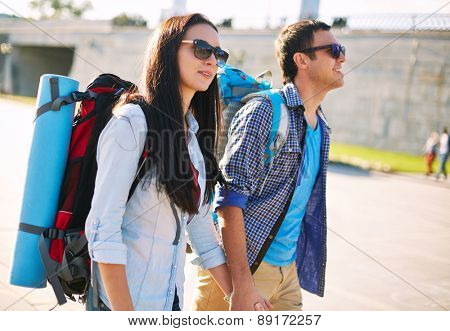 Young couple with rucksacks sightseeing