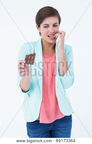 Woman choosing to eat chocolate or not on white background