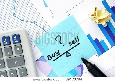 Papers with graphs, calculator and words sell and buy.