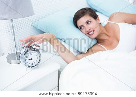 Happy woman extending hand to alarm clock at home in the bedroom