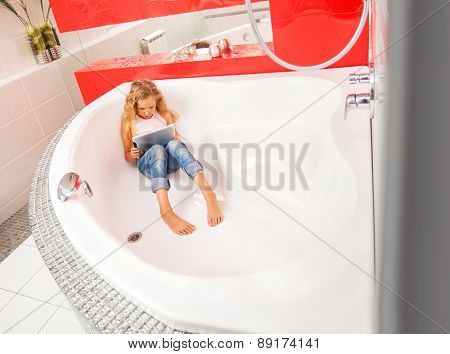 Girl hiding in the bathroom, playing in tablet. Computer Addiction, gambling, lie