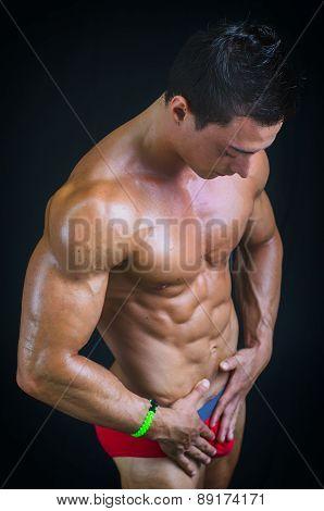 Profile of muscular bodybuilder relaxed in underwear