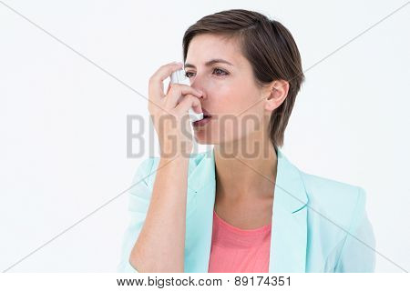 Pretty woman using her inhaler on white background