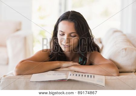 Pretty brunette reading magazine on the couch at home in the living room