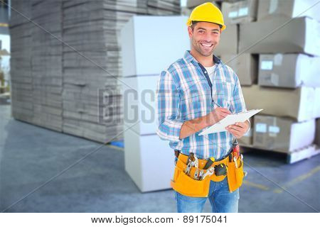 Portrait of smiling handyman writing on clipboard against cardboard boxes in warehouse