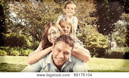 Happy family members lying on each other in the park smiling at camera