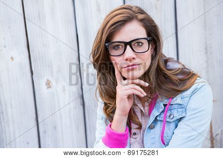Thoughtful woman looking at camera against wooden planks