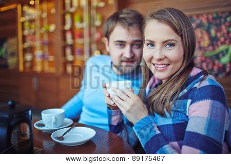 Pretty girl with cup of tea looking at camera on background of her boyfriend