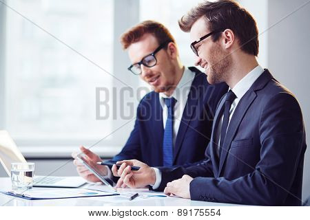 Young businessman explaining data to colleague at meeting