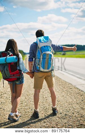 Rear view of hitch-hiking couple with rucksacks