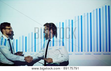 Young businessmen with touchpads handshaking by wall with chart on it